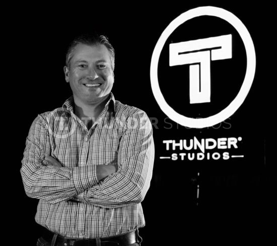 rodric david standing at thunder studios logo