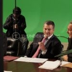 Inbetween shots during filming, Rodric David sits at at a boardroom table with a green screen backdrop.