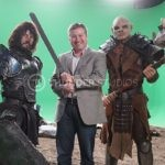 Behind the scenes of 'From the Veil', Rodric David poses in front of green screen with a knight and an orc